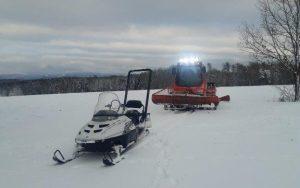 Motorschlitten und Pistenraupe im Schnee